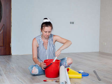 The woman in the room is sitting on the floor and stirring Wallpaper glue in a red bucket.