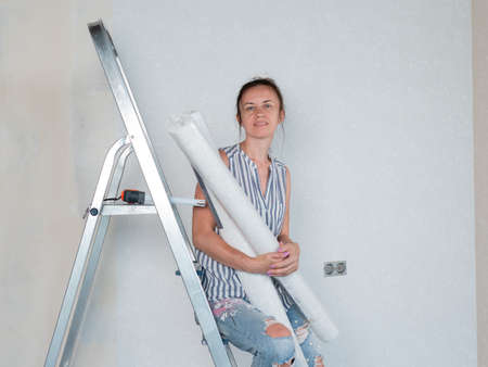 A woman with rolls of Wallpaper in the room smiles. Repairs in the apartment. Wallpapering in the room.
