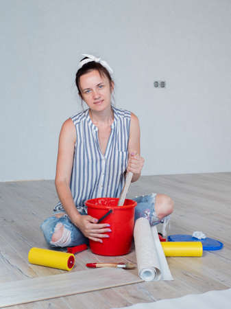 Portrait of a woman sitting on the floor of a room and stirring Wallpaper glue in a bucket. Concept of renovation in the apartment. Banco de Imagens