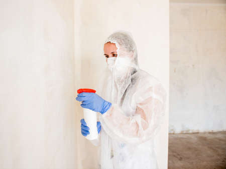A woman in a protective suit sprays the walls of an apartment with a chemical agent to remove mold.