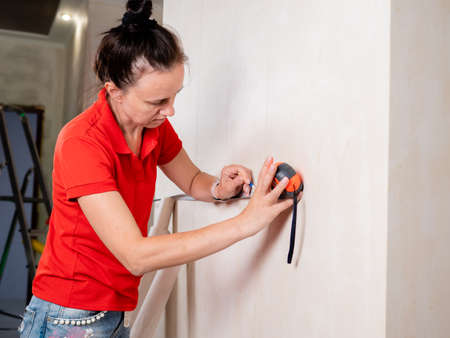 A woman uses a measuring tape measure to measure the wall for wallpapering. Reklamní fotografie