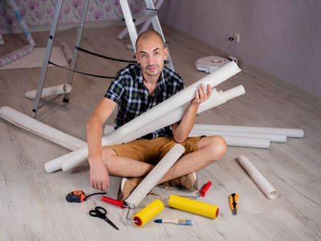 Portrait of a man on the floor with rolls of Wallpaper in his hands on the background of a stepladder. 写真素材