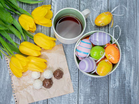 Easter eggs and tulips are on the table. View from above. Tea in a white cup and chocolates Stok Fotoğraf