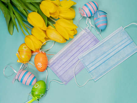 A bouquet of yellow tulips next to a medical mask and Easter eggs on a bright blue background. Stok Fotoğraf