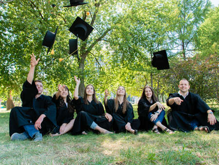 Happy student friends in mantle sit on the grass in the university park. Graduates throw their academic cap up