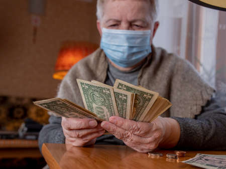 An elderly woman counts the remaining money. Economic crisis, poverty of the elderly.