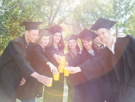 Outdoors photo of cheerful young graduate students fooling around and drinking champagne in university park Stok Fotoğraf