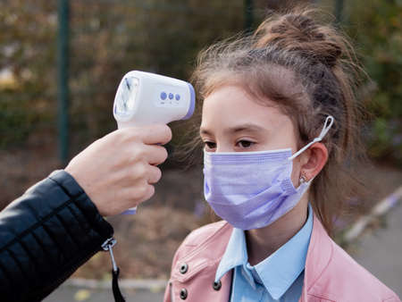 A sad Little Girl gets a temperature check outside the school as it reopens after being blocked . People are checking their body temperature with a non-contact thermometer, the new norm