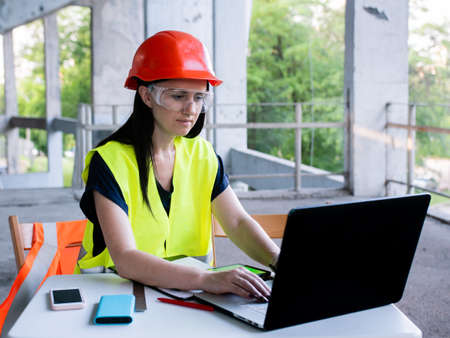 A female builder in an orange helmet sits on a construction site with a computer. The foreman checks the process of building a house.