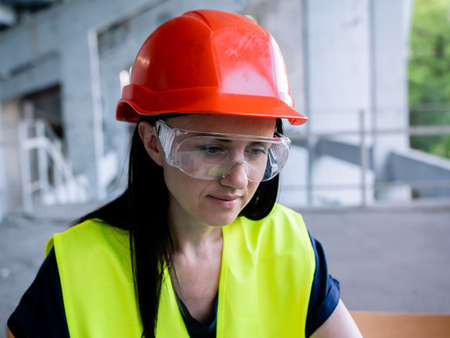 Woman architect in protective helmet and goggles working on personal computer on new project at construction site Stok Fotoğraf