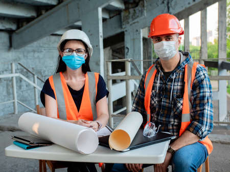 An architect and foreman in medical masks at a meeting to agree on the construction of a building. Social distancing Stok Fotoğraf