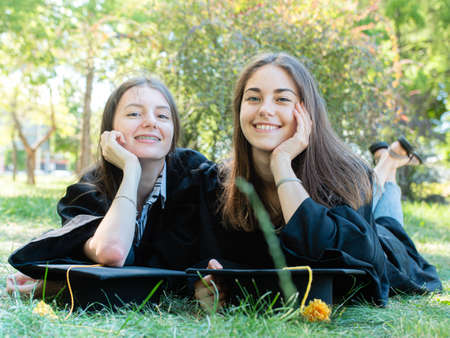 two university graduates in robes and academic caps lie on the lawn in the park and smile happily