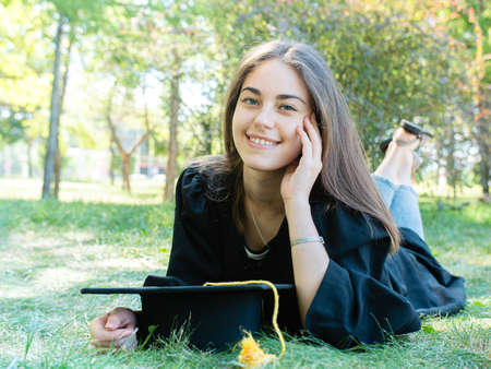 Young beautiful girl student in a mantle lies on the lawn and smiles happily Stok Fotoğraf