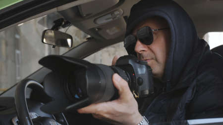 The concept spy or private detective takes photos with a long-focus lens from the car window. Stok Fotoğraf