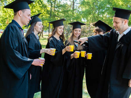 In the open air among the trees, a group of cheerful young graduate students in a black mantle of a graduate, who fool around, have fun and drink champagne.