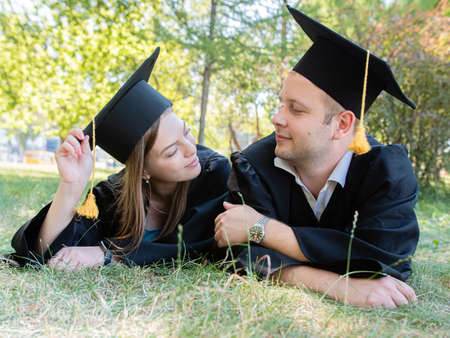 Happy loving couple of graduates in mantles lie on the lawn in the park of the university