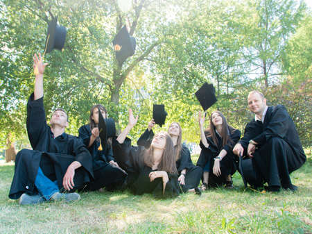 A group of young graduate students in gowns sitting in the park on the lawn cheerfully toss an academic cap up into the air
