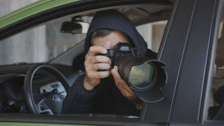 A private detective or photojournalist secretly takes photos from a car window with a long-focus lens. Stok Fotoğraf