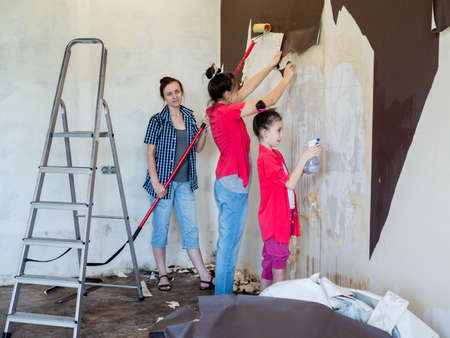 Mother and daughters together make repairs in the apartment, and stripped from the walls of the old Wallpaper. Stok Fotoğraf