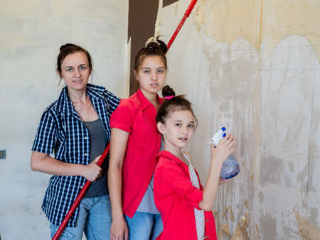 Mother with two daughters in the room is moistened with water the old Wallpaper with a roller and spray. Stok Fotoğraf