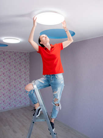 A woman in a childrens room sets a ceiling lamp.