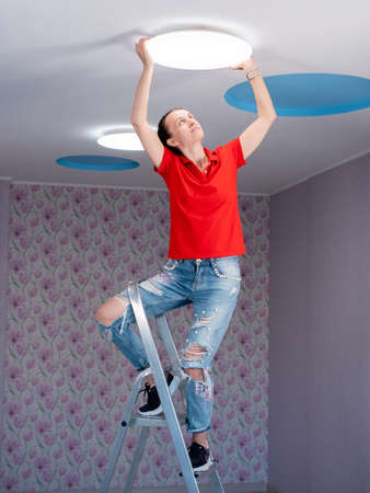 The woman in the room sets the led ceiling light.
