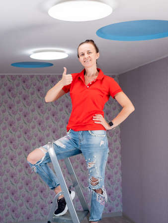 Happy woman installed led light on the ceiling smiles and points to the ceiling with her hands. Stok Fotoğraf