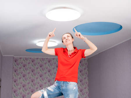 Concept update of the ceiling lamp in the childrens room. A happy Woman on a stepladder points to the ceiling.