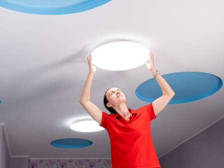 The girl hangs a ceiling lamp in the room.
