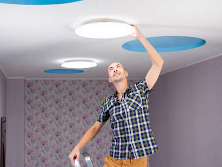 A man with a stepladder sets the ceiling lamp in the room.