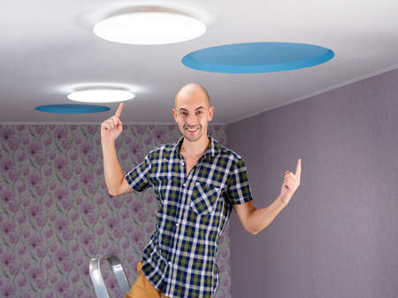 The concept of the man on the ladder is delighted with the installation of led lamp to the ceiling. Stok Fotoğraf