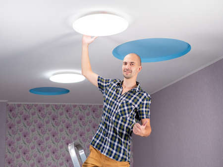 The man on the stepladder replaced the led light on the ceiling and is happy with the work done. Stok Fotoğraf