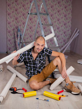 Portrait of a man on the floor with rolls of Wallpaper in his hands on the background of a stepladder. Stok Fotoğraf