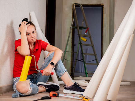 A woman sits on the floor and is sad because of the heavy repairs in the apartment. Wallpapering in the room.