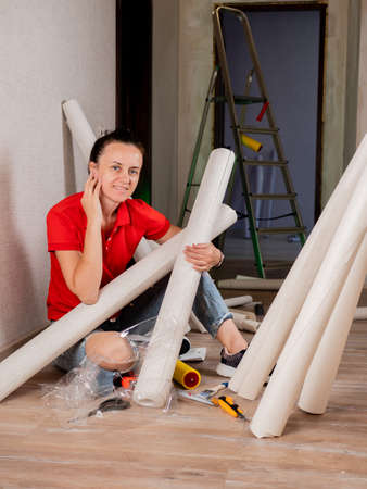A woman is sitting on the floor in a room with rolls of Wallpaper. Concept of renovation in the apartment.