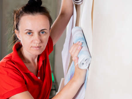 Portrait of a woman trying on rolls of Wallpaper to the wall. Wallpapering on the wall.