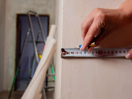 Repairs in the apartment. Close-up of a tape measure and pencil in womens hands. Measuring the walls in a room.