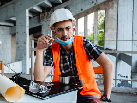 A concerned male civil engineer in a protective medical mask sits at a table at a construction site. Smoke break and reflection. Stok Fotoğraf
