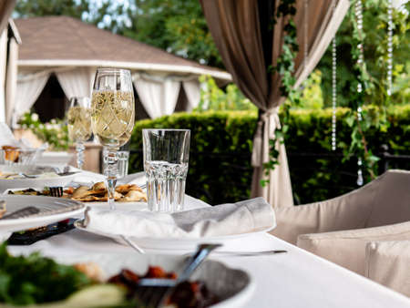 Glasses of champagne on a set table in an open-air restaurant.