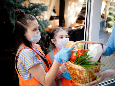 Teenage girls volunteers deliver food packages for the poor during the quarantine period. Stok Fotoğraf