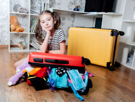 Little girl with suitcase ready for travel.