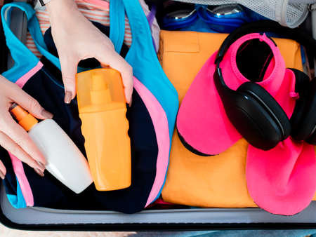 A woman collects a suitcase going on vacation to the sea.