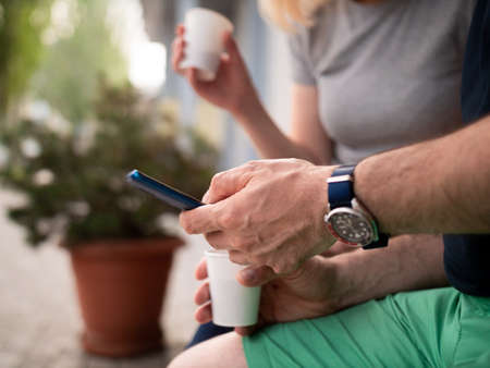 Close-up of a mans hands with a smartphone. Coffee break in the outdoors.