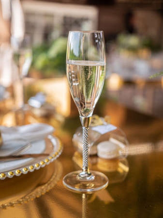 Close-up of a champagne glass in the gold decoration of a sumptuously decorated banquet table.