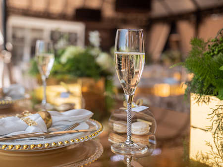 A glass of champagne on the terrace in an expensive restaurant on a set table for guests of honor.