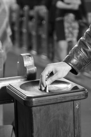 Inserting a banknote into donation box Standard-Bild