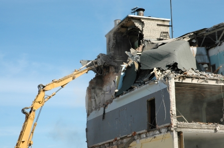 deconstruct: machine taking down an old building