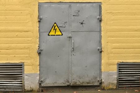 voltage gray: Danger high voltage sign on a rusty metal door
