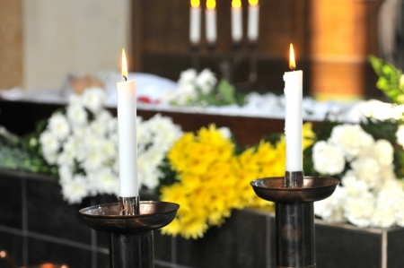 cremation: A burning candle with a coffin and a flower-arrangement