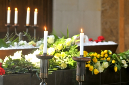 A burning candle with a coffin and a flower-arrangement